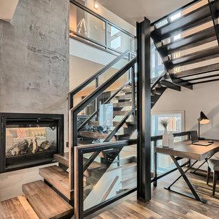 """Idee per una grande scala a """"U"""" contemporanea con pedata in legno, alzata in vetro e parapetto in metallo"""