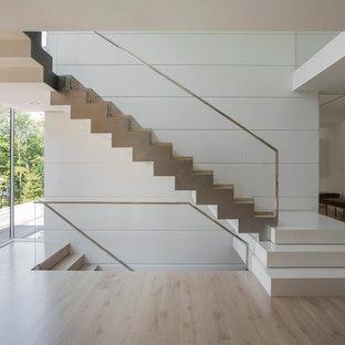 """Foto di una grande scala a """"L"""" minimalista con pedata in legno"""
