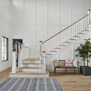 フェニックスの広い木のカントリー風おしゃれなかね折れ階段 (フローリングの蹴込み板、木材の手すり) の写真