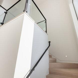 Modelo de escalera en L y madera, minimalista, grande, con escalones de madera, contrahuellas de madera, barandilla de metal y madera