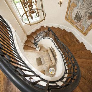 Ejemplo de escalera de caracol, rural, grande, con escalones de madera, contrahuellas de madera y barandilla de madera
