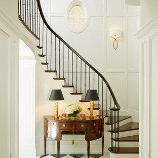 Imagen de escalera curva, tradicional, con escalones de madera, contrahuellas de madera pintada y barandilla de metal