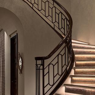 ダラスの広いライムストーンのトランジショナルスタイルのおしゃれなサーキュラー階段 (ライムストーンの蹴込み板、金属の手すり) の写真