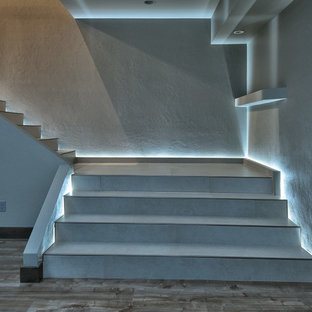 """Foto di una grande scala a """"L"""" minimalista con pedata piastrellata e alzata piastrellata"""