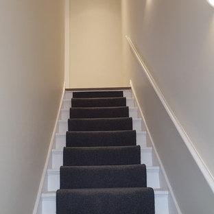 Foto de escalera recta, actual, pequeña, con escalones enmoquetados, contrahuellas enmoquetadas y barandilla de madera