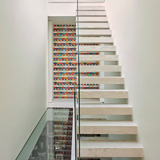 This is an example of a modern wood straight staircase in London with open risers and glass railing.