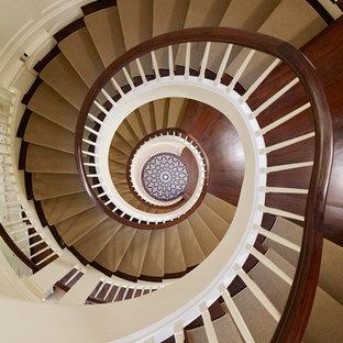 Пример оригинального дизайна интерьера: огромная лестница в классическом стиле с деревянными ступенями и крашенными деревянными подступенками
