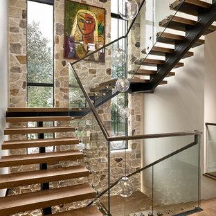 Immagine di una grande scala sospesa contemporanea con pedata in legno, nessuna alzata e parapetto in vetro