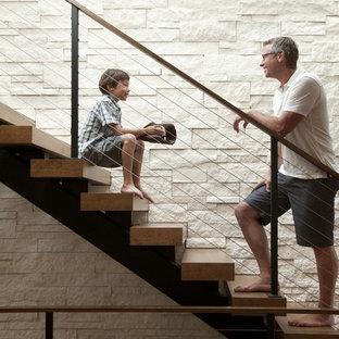 Стильный дизайн: лестница в современном стиле с перилами из тросов и деревянными ступенями без подступенок - последний тренд