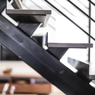 Ejemplo de escalera en L, minimalista, sin contrahuella, con escalones de madera