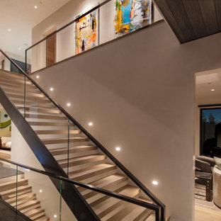 Ispirazione per un'ampia scala a rampa dritta contemporanea con pedata in legno, nessuna alzata e parapetto in vetro