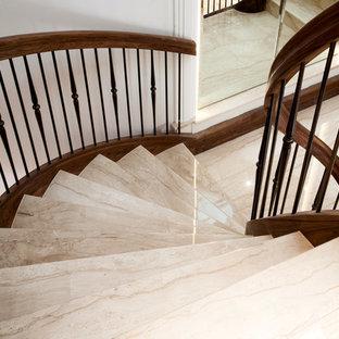 Diseño de escalera curva, clásica, grande, con escalones de mármol, contrahuellas de madera y barandilla de varios materiales