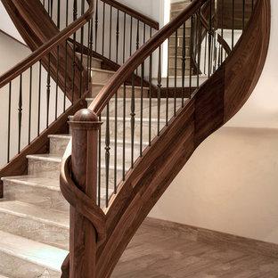 Modelo de escalera curva, tradicional, grande, con escalones de mármol, contrahuellas de madera y barandilla de varios materiales