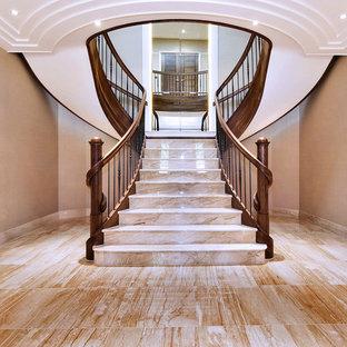 Modelo de escalera curva, clásica, grande, con escalones de mármol, contrahuellas de madera y barandilla de varios materiales