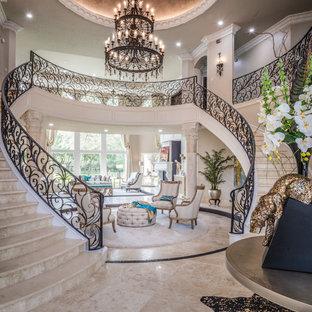 Diseño de escalera en U, clásica, grande, con escalones de travertino, contrahuellas de travertino y barandilla de metal