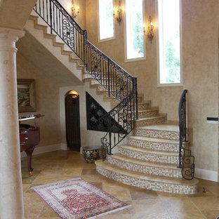 Diseño de escalera curva, tradicional, extra grande, con escalones de travertino, contrahuellas con baldosas y/o azulejos y barandilla de metal