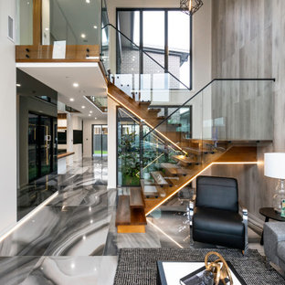 Photo of a contemporary wood staircase in Sydney with open risers and glass railing.