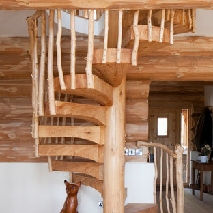 Rustic wood spiral staircase in West Midlands with open risers.
