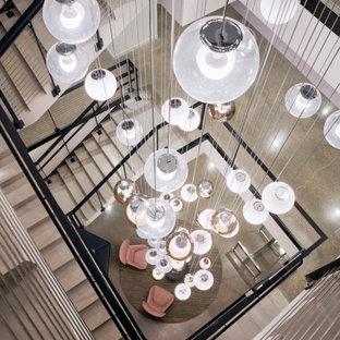 """Immagine di un'ampia scala a """"U"""" minimalista con pedata in legno, alzata in legno, parapetto in cavi e pareti in legno"""