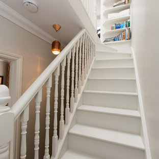 Classic painted wood straight wood railing staircase in London with painted wood risers.