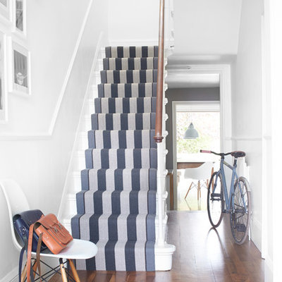 Example of a transitional painted u-shaped staircase design in London with painted risers