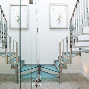 На фото: изогнутая лестница в современном стиле с стеклянными ступенями без подступенок с