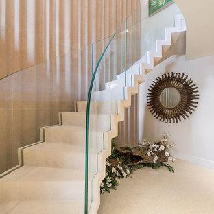 Modelo de escalera curva, clásica renovada, grande, con escalones de piedra caliza, contrahuellas de piedra caliza y barandilla de vidrio