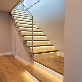 Ispirazione per una scala a rampa dritta moderna di medie dimensioni con pedata in legno, alzata in legno e parapetto in vetro