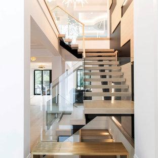 トロントの巨大なタイルのコンテンポラリースタイルのおしゃれな階段 (ガラスの手すり) の写真