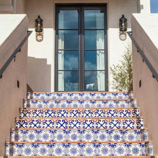 ロサンゼルスのテラコッタの地中海スタイルのおしゃれな直階段 (タイルの蹴込み板、金属の手すり) の写真