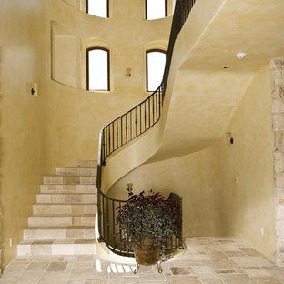 Стильный дизайн: изогнутая лестница в средиземноморском стиле с ступенями из травертина, подступенками из травертина и металлическими перилами - последний тренд