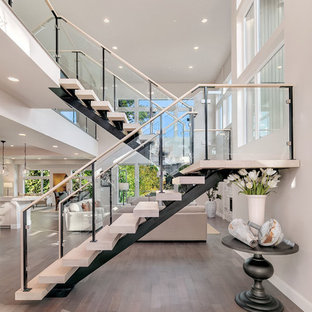 Example of a trendy wooden u-shaped open and glass railing staircase design in Seattle