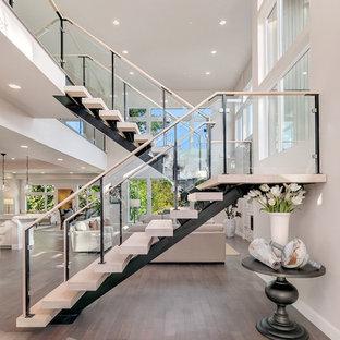 Diseño de escalera en U, actual, sin contrahuella, con escalones de madera y barandilla de vidrio