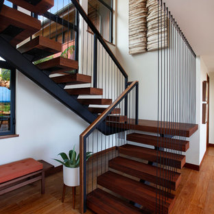 Large island style wooden floating open and cable railing staircase photo in Denver