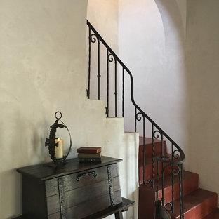 Ejemplo de escalera en L, de estilo americano, grande, con escalones de hormigón, contrahuellas de hormigón y barandilla de metal