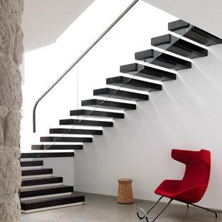 Diseño de escalera suspendida, contemporánea, sin contrahuella, con barandilla de vidrio