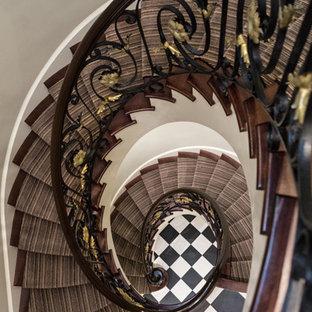 Immagine di una grande scala a chiocciola classica con pedata in moquette, alzata in moquette e parapetto in materiali misti