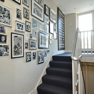 Traditional carpeted u-shaped staircase in London with carpeted risers.