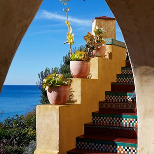 Пример оригинального дизайна интерьера: лестница в стиле фьюжн с ступенями из плитки и подступенками из плитки