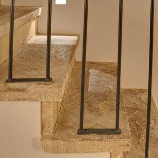 ロンドンの広いライムストーンのトラディショナルスタイルのおしゃれな直階段 (ライムストーンの蹴込み板、金属の手すり) の写真