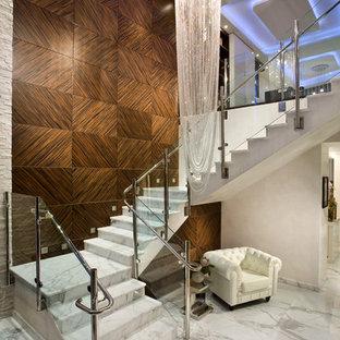 Modern inredning av en stor u-trappa i marmor, med sättsteg i marmor och räcke i glas