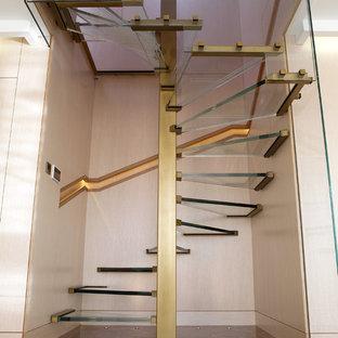Immagine di una scala a chiocciola design con pedata in vetro e nessuna alzata