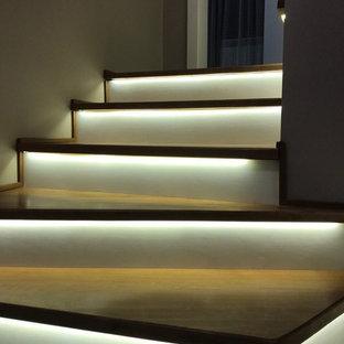 Diseño de escalera curva, actual, grande, con escalones de madera, contrahuellas de vidrio y barandilla de vidrio