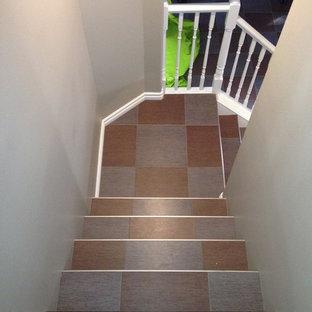 Ejemplo de escalera en L, contemporánea, de tamaño medio, con escalones con baldosas y contrahuellas de madera