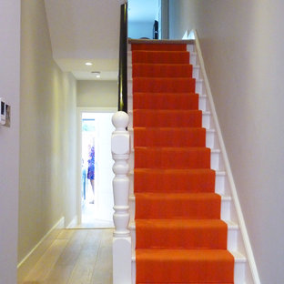 Example of a mid-sized transitional painted straight staircase design in London with wooden risers