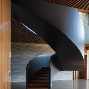 Idee per un'ampia scala a chiocciola minimalista con pedata in legno e alzata in cemento
