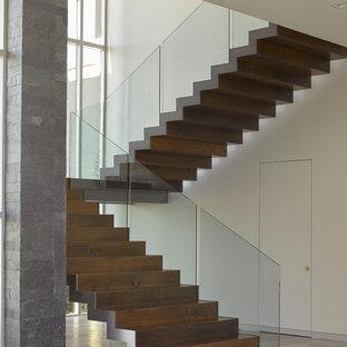 Diseño de escalera suspendida, contemporánea, grande, con escalones de madera, contrahuellas de madera y barandilla de vidrio