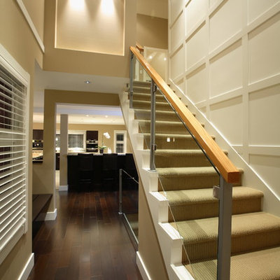 Large transitional painted straight glass railing staircase photo in Vancouver with painted risers