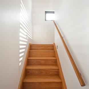 """Immagine di una piccola scala a """"U"""" minimalista con pedata in legno, alzata in legno e parapetto in legno"""