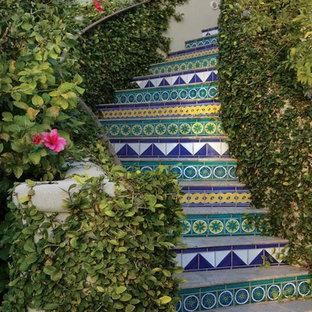 フェニックスの中サイズのタイルの地中海スタイルのおしゃれなサーキュラー階段 (タイルの蹴込み板) の写真